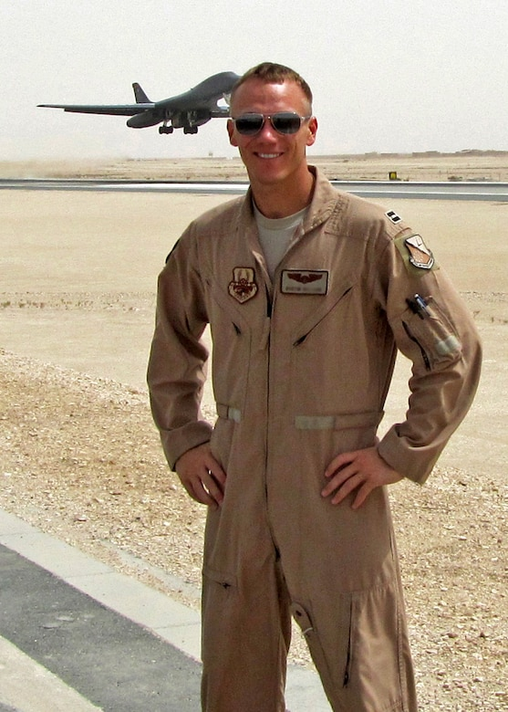 Capt. Dustin poses for a photo during his deployment to Afghanistan in 2012 where he served as an aircraft commander for a B-1B Lancer. In the background a Lancer takes flight. Dustin and his aircrew have been named the Air Force's 2012 bomber crew of the year and were awarded the Air Force Association's Gen. Curtis E. Lemay Award. (Courtesy photo)