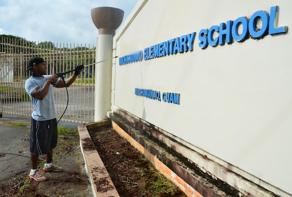 YIGO, Guam—Tech. Sgt. Bryan Johnson, 36th Force Support Squadron lodging superintendent, pressure-washes an entrance sign during a school beautification project at the Machananao Elementary School in Yigo, Guam, Aug. 14, 2013. Members of Team Andersen joined forces with U.S. Army units to assist Machananao Elementary and other schools in the community with restoration, landscaping and trash clean-up before the start of the school year. (U.S. Air Force photo by Staff Sgt. Benjamin Wiseman/Released)