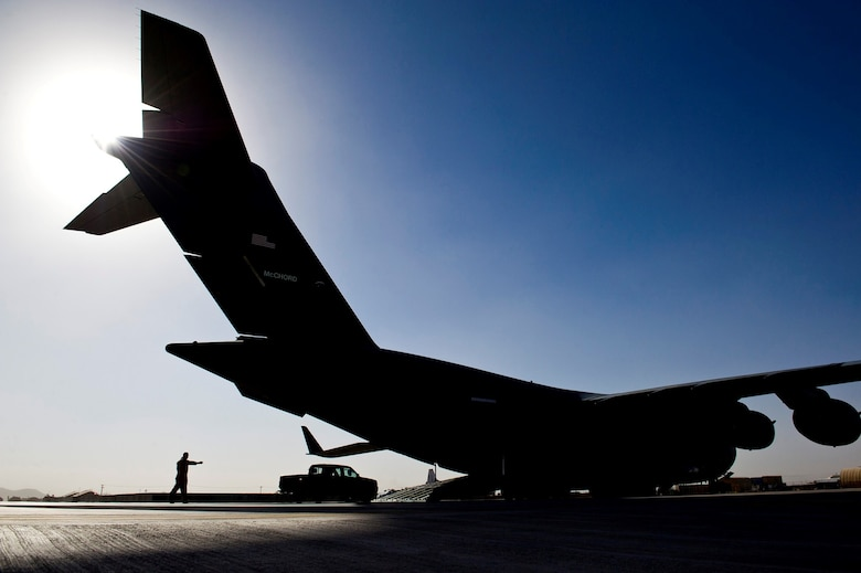 Tech. Sgt. Gary Washington off-loads vehicles from a C-17 Globemaster III during an airlift mission July 25, 2013, at Forward Operating Base Shindand in Herat, Afghanistan. The C-17 is capable of rapid strategic and tactical delivery of troops and any type of cargo to main operating and forward operating bases in Afghanistan. The aircraft can perform airlift and airdrop missions and transport ambulatory patients during aeromedical evacuations when required.  Washington is a loadmaster assigned to the 316th Expeditionary Airlift Squadron. (U.S. Air Force photo/Staff Sgt. Marleah Miller)