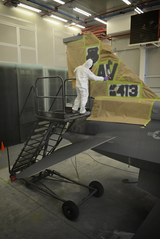Francesco Di Carlo paints the tail end of an F-16 Fighting Falcon Aug. 13, 2013, at Aviano Air Base, Italy. Corrosion control focuses on preventative maintenance by sanding down and repainting aircraft through the use of special polyurethane paint, which helps protect the metal from environmental stressors. Di Carlo is a 31st Maintenance Squadron corrosion technician. (U.S. Air Force photo/Senior Airman Jessica Hines)