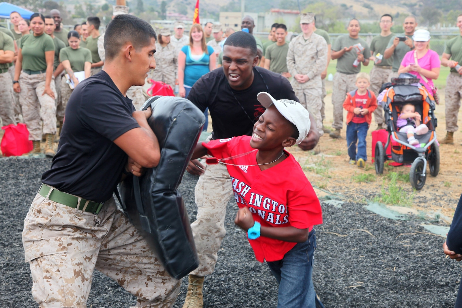 A Marine's son practices Marine Corps Martial Arts with Marines from 1st Supply Battalion, Combat Logistics Regiment 15, 1st Marine Logistics Group, during the battalion's Johnny Wayne Day aboard Camp Pendleton, Calif., Aug. 9, 2013. At the family day, the children of Marines and sailors participated in a number of events that simulated what their parents might experience on a day-to-day basis as a member of the military.