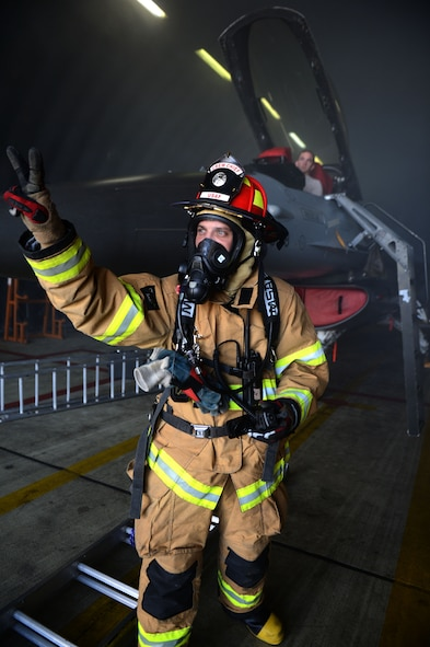 SPANGDAHLEM AIR BASE, Germany – U.S. Air Force Tech. Sgt. Michael Tellish, 52nd Civil Engineer Squadron crew chief from Pittsburg, communicates to his fellow firefighters with hand gestures during an aircraft fire training exercise Aug. 14, 2013. Communicating with an oxygen mask is difficult, but fire protection Airmen use any means necessary to relay a message during an incident such as this. (U.S. Air Force photo by Airman 1st Class Gustavo Castillo/Released)