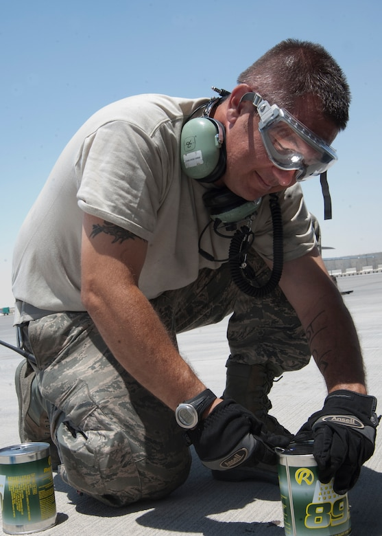 Tech. Sgt. Derrick Melrose opens a can of oil before pouring it into a KC-135 Stratotanker engine during a thru flight inspection at the 379th Air Expeditionary Wing in Southwest Asia, Aug. 13, 2013. Melrose is a 340th Expeditionary Aircraft Maintenance Unit crew chief deployed from General Mitchell Air National Guard Base, Wis., and hails from Bristol, Wis. (U.S. Air Force photo/Senior Airman Bahja J. Jones)