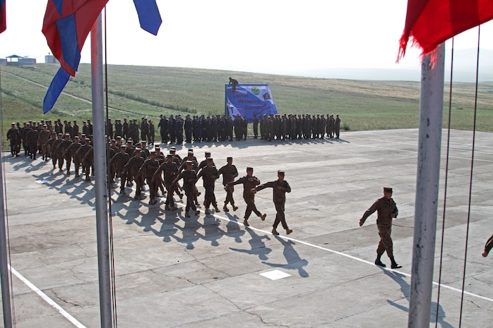 Mongolian Armed Forces service members, Mongolian General Police and U.S. Marines with Law Enforcement Battalion, 3rd Marine Expeditionary Force Headquarters Group, III Marine Expeditionary Force, march during the pass and review portion of the opening ceremony of Non-Lethal Weapons Executive Seminar (Knoles) in Five Hills Training Area, Mongolia, August 17, 2013. Knoles is a regularly scheduled field training exercise and leadership seminar sponsored annually by U.S. Marine Corp Forces Pacific, and it is designed to promote awareness and effective use of non-lethal weapons as a tool to maintain order in low-intensity or civil unrest situations.(U.S. Marine Corps Photo by Sgt John M. Ewald/released)