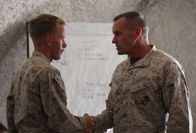 Brigadier Gen. Vincent A. Coglianese, commanding general of 1st Marine Logistics Group, shakes hands with Cpl. Thomas Evans, a squad leader with Combat Logistics Battalion 11, Combat Logistics Regiment 17, 1st MLG, for his hard work and discipline as squad leader at Marine Corps Air Ground Combat Center, Calif., Aug. 9, 2013. Coglianese came aboard MCAGCC to observe the battalion's field exercise.
