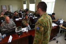 Australian Army Maj. Scott McMahon, acting as the executive officer for the Multinational Brigade, delivers a quick brief to his staff officers during Khaan Quest's command post exercise, Aug. 12. Khaan Quest, a multinational peacekeeping exercise hosted annually by the Mongolian Armed Forces and co-sponsored by U.S. Marine Corps Forces Pacific and U.S. Army Pacific, is the latest in a continuing series of exercises designed to promote regional peace and security. MARFORPAC is the U.S. executive for this year's exercise, which has been taking place since 2003. Khaan Quest 2013 officially ended Aug. 14. McMahon is from Puckapunyal, Victoria, Australia.