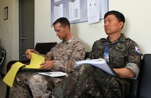 U.S. Marine Capt. Albert Bellamy and Republic of Korea Army Col. Seoko Yoon listen to a brief during Khaan Quest's command post exercise, Aug. 12. Khaan Quest, a multinational peacekeeping exercise hosted annually by the Mongolian Armed Forces and co-sponsored by U.S. Marine Corps Forces Pacific and U.S. Army Pacific, is the latest in a continuing series of exercises designed to promote regional peace and security. MARFORPAC is the U.S. executive for this year's exercise, which has been taking place since 2003. Khaan Quest 2013 officially ended Aug. 14. Bellamy, serving as a battalion operations officer for 2nd Battalion, 11th Marine Regiment during the CPX, is from Wadsworth, Ohio. Yoon served as the civil-military affairs officer for the multinational brigade's headquarters.