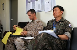 U.S. Marine Capt. Albert Bellamy and Republic of Korea Army Col. Seoko Yoon listen to a brief during Khaan Quest's command post exer