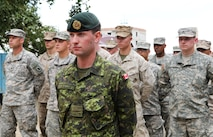 """Canadian Forces Capt. Patrick Reid, an engineer with 1 Engineer Support Unit, Joint Operational Support Group out of Kingston, Ontario, leads a multinational formation of U.S. Marines from 9th Engineer Support Battalion and Washington Army National Guard soldiers with 96th Troop Command, during a ribbon-cutting ceremony for the newly renovated Erdmiin Orgil School in Nalaikh district, Ulaanbaatar, Mongolia, Aug. 13. The project took place as part of exercise Khaan Quest 2013. Engineers from the U.S., Mongolia and Canada worked side-by-side to replace the roof, windows, front stairs and interior doors, """"re-stucco"""" the exterior walls, apply emulsion and repaint the building. They also tore down a structurally unsound concrete awning at the main entrance and built a handicap-accessible ramp at the front of the school."""