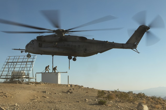 A CH-53E hovers and prepares to extract a container out of Observation Post Crampton in the Combat Center's training area Aug. 13, 2013. Marines with Combat Logistics Battalion 7 and HMH-366 extracted communication gear. The units used the extraction as a training exercise.