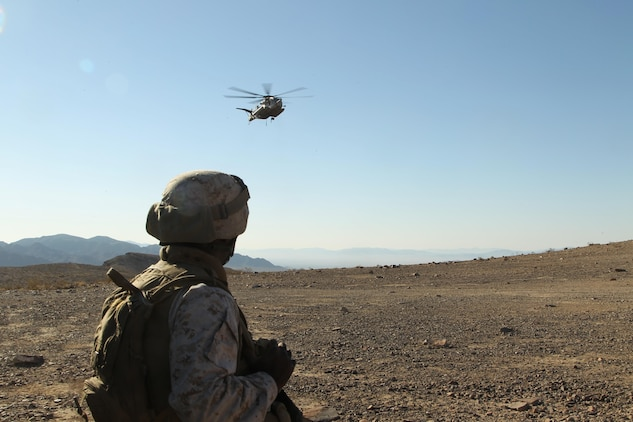 A Marine with Combat Logistics Battalion 7 watches as a CH-53 approaches a container at Observation Post Crampton in the Combat Center's training area Aug. 13, 2013. Marines with Combat Logistics Battalion 7 and HMH-366 extracted communication gear. The units used the extraction as a training exercise.