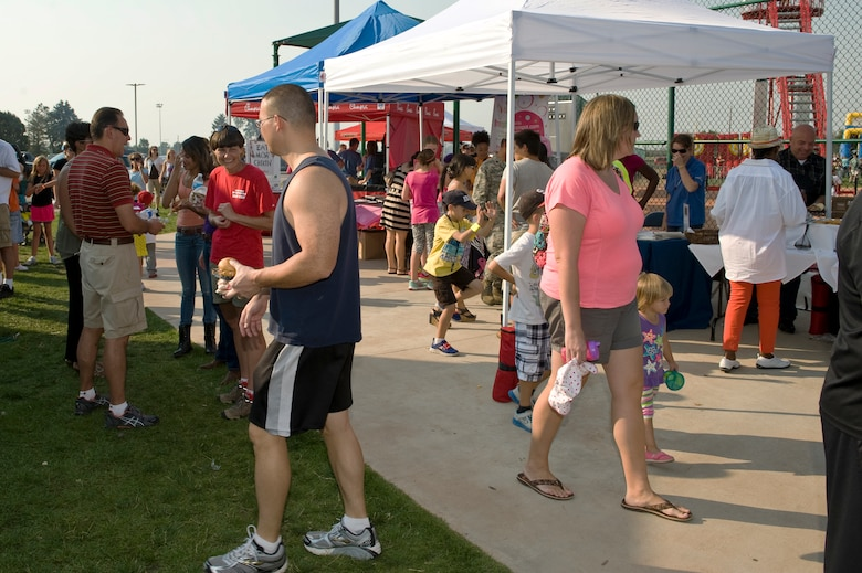 Members of Team Buckley enjoy food and activities during Fun Fest Aug. 13, 2013, at the softball fields on Buckley Air Force Base. The Fun Fest community fair is an annual celebration that included booths from various community groups, base agencies, and free food. (U.S. Air Force photo by Senior Airman Phillip Houk/Released)