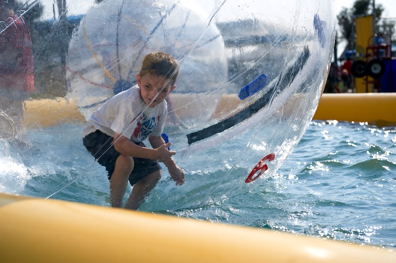 The son of a 460th Space Communications Squadron member walks on top of water while inside of a water ball during Fun Fest Aug. 13, 2013, at the softball fields on Buckley Air Force Base, Colo.  Fun Fest is Buckley's annual birthday celebration which includes a field day and community fair. (U.S. Air Force photo by Senior Airman Phillip Houk/Released)
