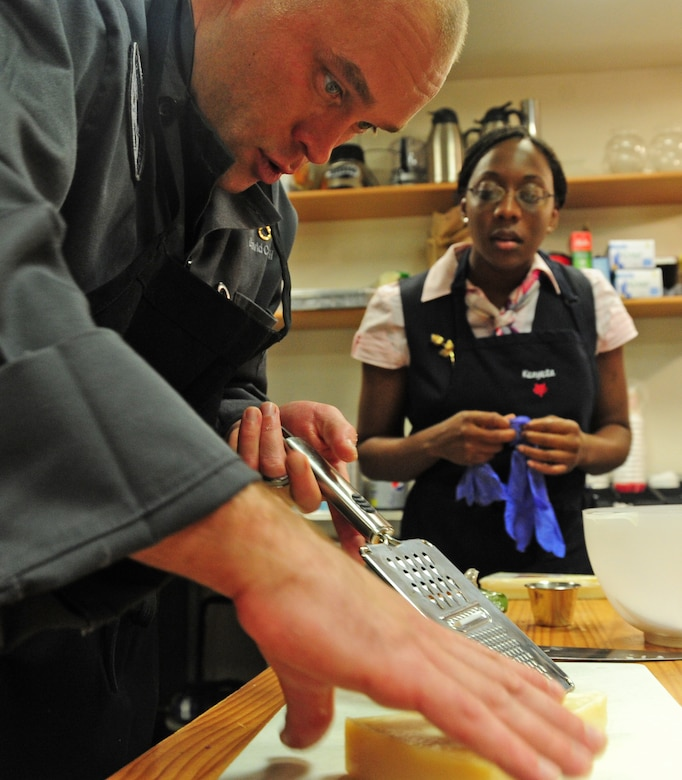 Army Staff Sgt. David Cantwell, U.S. Army Priority Air Transport flight steward, teaches Air Force Staff Sgt. Kenyeta Brackett, 1st Airlift Squadron flight attendant, different cooking techniques during a joint service culinary training session on Joint Base Andrews, Md., Aug. 14, 2013. The Soldiers and Airmen traded ideas and methods and enjoyed each other's culinary creations afterward. (U.S. Air Force photo/Airman 1st Class Erin O'Shea)