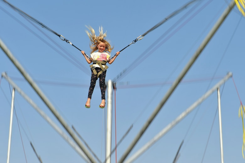The daughter of a 460th Force Support Squadron member jumps on a bungee trampoline during Fun Fest Aug. 16, 2013, at the softball fields on Buckley Air Force Base, Colo. Fun Fest is an annual Buckley birthday celebration which includes a day full of field-day activities and a community fair. (U.S. Air Force photo by Senior Airman Phillip Houk/Released)
