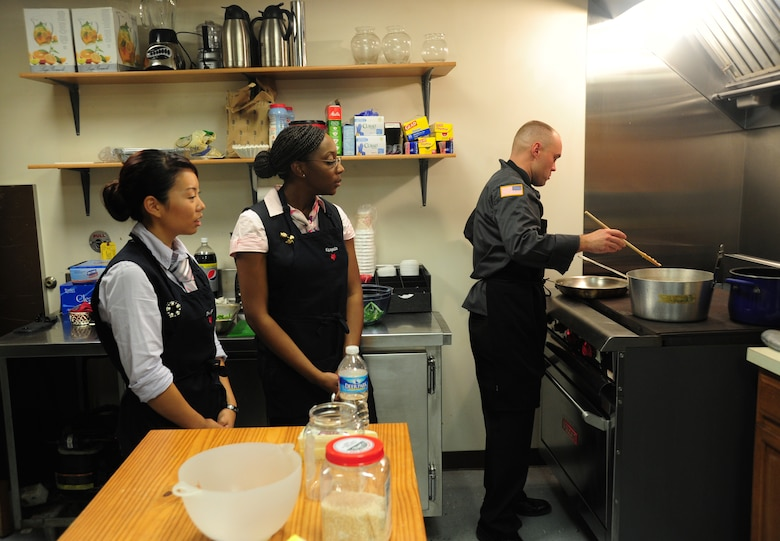 Staff Sgt. Christine Kim and Kenyeta Brackett, 1st Airlift Squadron flight attendants, observe Army Staff Sgt. David Cantwell, U.S. Army Priority Air Transport flight steward, as he prepares a rice dish during a joint service culinary training session on Joint Base Andrews, Md., Aug. 14, 2013. Army stewards and Air Force flight attendants conducted a training class to exchange knowledge and skills from one another. (U.S. Air Force photo/Airman 1st Class Erin O'Shea)