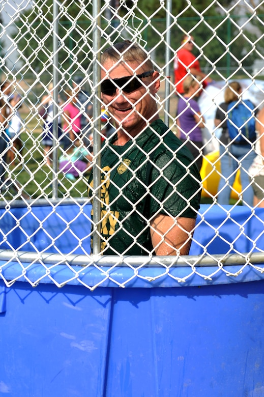 Chief Master Sgt. Craig Hall, 460th Space Wing command chief, rises up in the dunk tank after being immersed in water the during Fun Fest Aug. 16, 2013, at the softball fields on Buckley Air Force Base, Colo. The 460th Space Wing celebrated its ninth birthday with Fun Fest, a day filled with sport competitions and a community fair. (U.S. Air Force photo by Airman 1st Class Riley Johnson/Released)