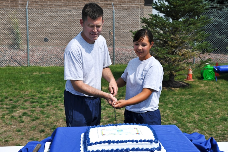 Col. Dan Wright, 460th Space Wing commander, and Airman Amanda Belarde, 460th SW Legal Office paralegal, cut a birthday cake at Fun Fest Aug. 16, 2013, at the softball fields on Buckley Air Force Base, Colo. Belarde was chosen to cut the cake because she is the Airman with the least amount of time-in-service assigned to the 460th SW. (U.S. Air Force photo by Airman 1st Class Riley Johnson/Released)