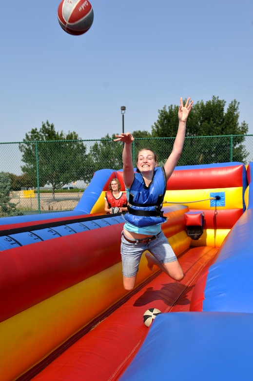 A Team Buckley spouse attempts a basket while playing on an inflatable bungee game at Fun Fest Aug. 16, 2013, at the softball fields on Buckley Air Force Base, Colo. The 460th Space Wing celebrated its ninth birthday with Fun Fest, a day filled with sport competitions and a community fair. (U.S. Air Force photo by Airman 1st Class Riley Johnson/Released)
