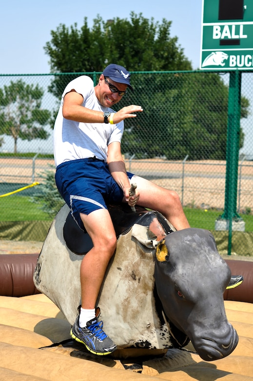 Lt. Col. Derek Bright, 460th Operations Group, channels his inner cowboy while riding a mechanical bull during Fun Fest Aug. 16, 2013, at the softball fields on Buckley Air Force Base, Colo. The 460th Space Wing celebrated its ninth birthday with Fun Fest, a day filled with sport competitions and a community fair. (U.S. Air Force photo by Airman 1st Class Riley Johnson/Released)