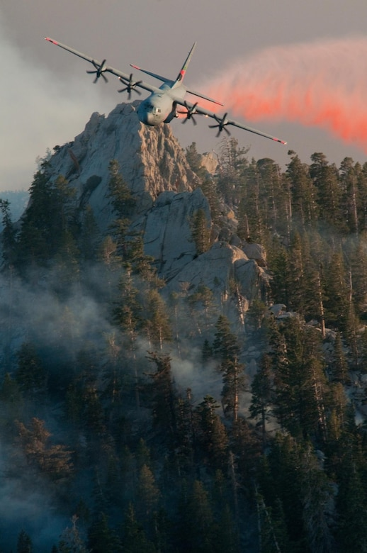 A C130J Super Hercules from the 146th Airlift Wing in Port Hueneme, Calif., drops a line of retardant over the trees July 19, 2013, in the mountains above Palm Springs. The 146th AW was activated July 18 to support CAL Fire and CAL OES on the Mountain fire and other potential wildfire activity throughout the state.
