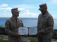 SSgt Alex Polley holds his certificate of reenlistment with Marine Corps Activity Guam Officer in Charge Colonel Scott Loch.