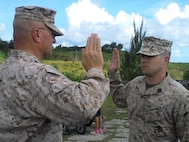 SSgt Alex Polley swears in with Marine Corps Activity Guam Officer in Charge Colonel Scott Loch during his reenlistment.