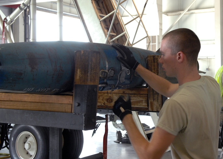 U.S. Air Force Airman 1st Class Zakk Bunting, 7th Munitions Squadron load crew member, inspects a Mark-82 air during a practice load Aug. 8, 2013, at Dyess Air Force Base, Texas. Load crew members are evaluated and recertified every month to ensure their weapon loading skills remain precise and up to Air Force standards. (U.S. Air Force photo by Senior Airman Shannon Hall/Released)