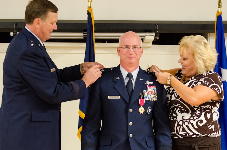 Maj. Gen. Mark Kraus' wife (right) and Kentucky's adjutant general, Maj. Gen. Edward Tonini, pin the rank insignia of major general to Kraus' uniform during a promotion ceremony at the Kentucky Air National Guard Base in Louisville, Ky., Aug. 18, 2013. Kraus is a Kentucky Air Guardsman who serves as Air National Guard assistant to the commander of U.S. Air Forces Central. (U.S. Air National Guard photo by Airman Joshua Horton)