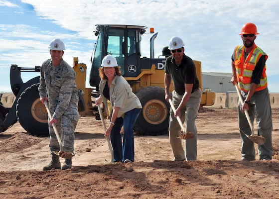 DAVIS-MONTHAN AFB, Ariz. – (From left to right) Lt. Col. Phil Acquaro, 42nd Electronic Combat Squadron commander; Michele Mickle, quality assurance representative in the U.S. Army Corps of Engineers Los Angeles District's Tucson Resident Office; Tony Gomez, 355th Civil Engineer Squadron lead architect; and Andrew Erquiaga, RSCI Group construction team lead, toss ceremonial shovels of dirt for the new EC-130H Simulator Training Operations Facility during a groundbreaking ceremony held Aug. 15 at Davis-Monthan Air Force Base. When it is complete in August 2014, the new facility will provide space for new EC-130H flight deck simulator, new EC-130H mission crew simulator and one relocated EC-130H mission crew simulator among its many benefits.