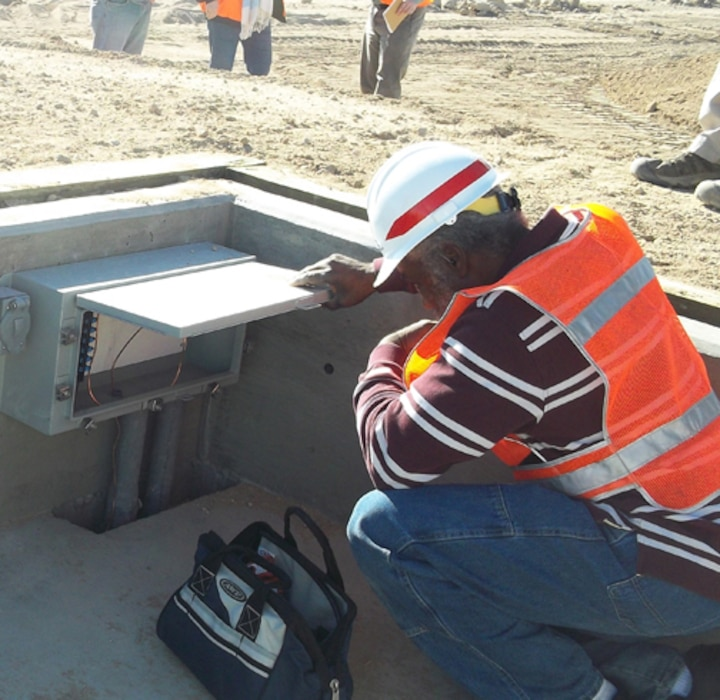 Huntsville Center electrical engineer William Strong, kneeling, performs a Construction Compliance Inspection at a Qualification Training Range on Fort Irwin, Calif., in January. The Army has tasked the organization's Range Training and Land Program to perform two mandatory inspections on new range construction before completion.