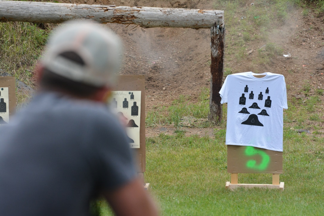 A rifle participant aims at his target during the 2nd Annual Explosive Ordnance Disposal Warrior 3-Gun Shoot at the Deerfield Rod and Gun Club in Deerfield, Wis., July 27, 2013. Attendees could buy t-shirts with smaller targets on them, for a chance to earn more points during the event. Money raised throughout the day was donated to the EOD Warrior Foundation, an organization that supports EOD warriors and their families, and maintains the EOD Memorial. (Air National Guard photo by Senior Airman Andrea F. Liechti)