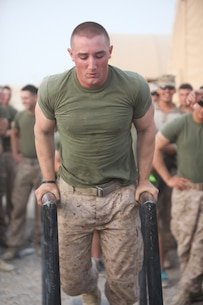 """Lance Cpl. Brendan Hennessy, 19, a rifleman with Company E, 2nd Battalion, 8th Marine Regiment, Regimental Combat Team 7, performs dips as part of the strong man competition held July 23. """"At the end of the day it's all about fitness and building camaraderie between Marines,"""" said Hennessy. """"Win or lose it was just for fun, and that's all that matters."""""""