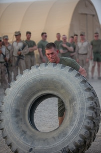 """Capt. Dylan Baker, a native of Aurora Colo., the company commander of Headquarters and Service Company, flips as tire 20 meters as part of the Strong Man Competition held July 23. """"Marines were asking to have some type of tournament like football or baseball,"""" said Sgt. Joseph Jennings, 27, the company police sergeant with Headquarters and Service Company, 2nd Bn., 8th Marines. """"So I figured having a strong man competition would be a great way start."""""""