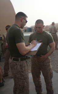 """Lance Cpl. Brendan Hennessy, 19, a rifleman with Company E, 2nd Battalion, 8th Marine Regiment, Regimental Combat Team 7, signs up for the weight lifting portion of the strong man competition. """"I used to do strongman competitions back in high school,"""" said the Lynbrook, N.Y., native. """"Once I really got into the competition, it was like being back in high school again."""""""
