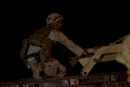 A Marine with Combat Logistics Regiment 2, Regional Command (Southwest), assists a hoist removing a broken mine roller from the road during a recovery operation near Camp Leatherneck, Afghanistan, July 26, 2013. The mine roller broke near the end of a day-long combat logistics patrol, launching a recovery operation to clear the road leading toward the base.