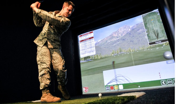 Senior Airman Dane Adams, 354th Communications Squadron cyber transport technician, practices his golf swing during Eielson City Center's opening March 29, 2013, Eielson Air Force Base, Alaska. The ECC gives Airmen and their families the opportunity for various activities in a central location on base.