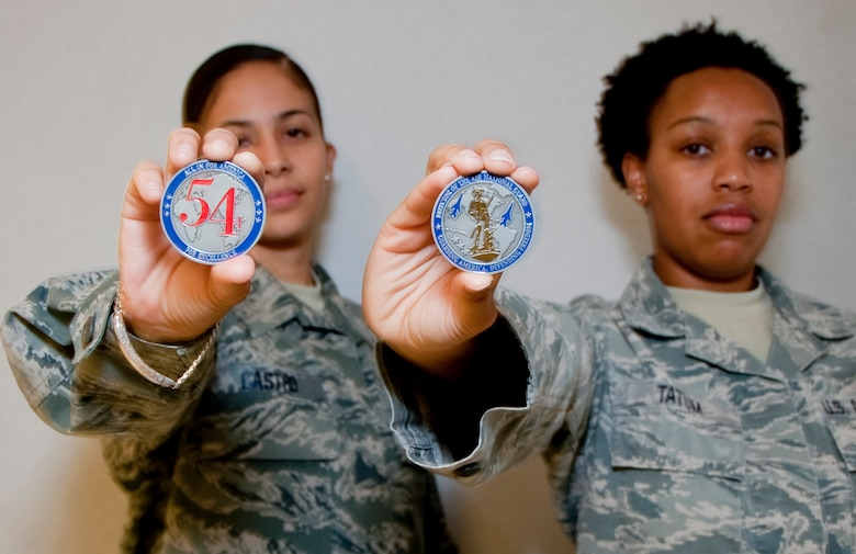 Master Sgt. Nora Castro and Tech. Sgt. Carolyn Tatum, 136th Airlift Wing, Texas Air National Guard, show off the coin they received from Lt. Gen. Stanley Clarke during his site visit at Naval Air Station Fort Worth Joint Reserve Base, Aug. 21, 2013. Lt. Gen. Clarke awarded the coins for serving with distinction. . (Air National Guard photo by Airman Cody Witsaman/released)
