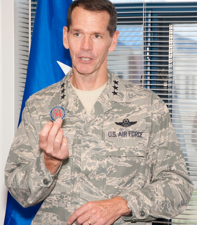 Lt. Gen. Stanley Clarke, director, Air National Guard show off his coin prior to rewarding the Airmen of the 136th Airlift Wing, Texas Air National Guard for serving with distinction at Naval Air Station Fort Worth Joint Reserve Base, Aug. 21, 2013 during his site visit. The number 54 signifies 50 States, three territories and one District. (Air National Guard photo by Airman Cody Witsaman/released)