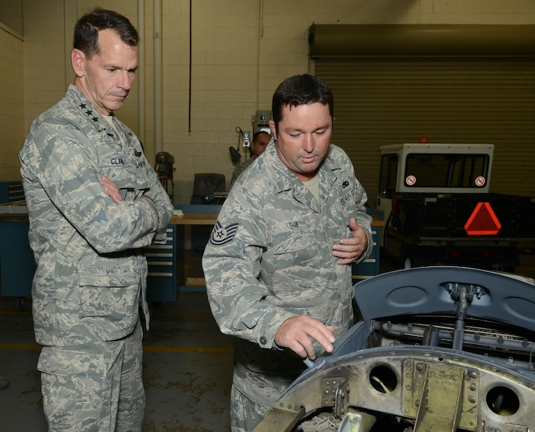 Lt. Gen. Stanley Clarke, director, Air National Guard, listens intently to Tech. Sgt. Jimmy Shaw, metals  fabrication technician, 136th Airlift Wing, Texas Air National Guard during his site visit at Naval Air Station Fort Worth Joint Reserve Base, Aug. 21, 2013. Shaw explains the process for repairing an engine cowling to Lt. Gen. Clarke. (Air National Guard photo by Senior Master Sgt. Elizabeth Gilbert/released)