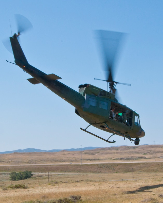 """130814-F-BR137-534 A UH-1N """"Huey"""" Helicopter carries tactical response force members back to Camp Guernsey, Wyo., after completion of launch facility recapture training at the Tango-09 Launch Facility, a deactivated Peacekeeper ICBM LF, Aug. 14, 2013. (U.S. Air Force photo by Airman 1st Class Jason Wiese)"""