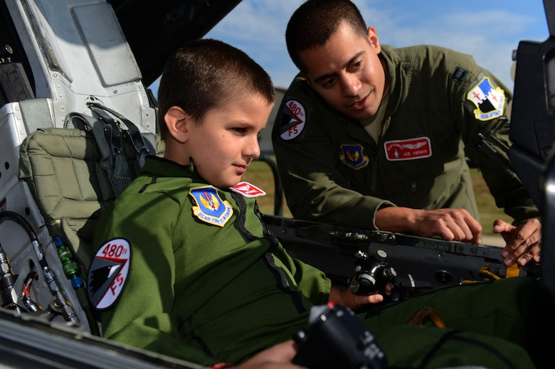 SPANGDAHLEM AIR BASE, Germany – U.S. Air Force Capt. Joseph Viegas, 480th Fighter Squadron pilot from Minneapolis, shows Stevie Frost, 9, the inside of an F-16 Fighting Falcon fighter Aircraft Aug. 16, 2013. Stevie spent 14 months in and out of a local German hospital undergoing chemotherapy and radiation treatments and is now 100 percent cancer free. (U.S. Air Force photo by Airman 1st Class Gustavo Castillo/Released)