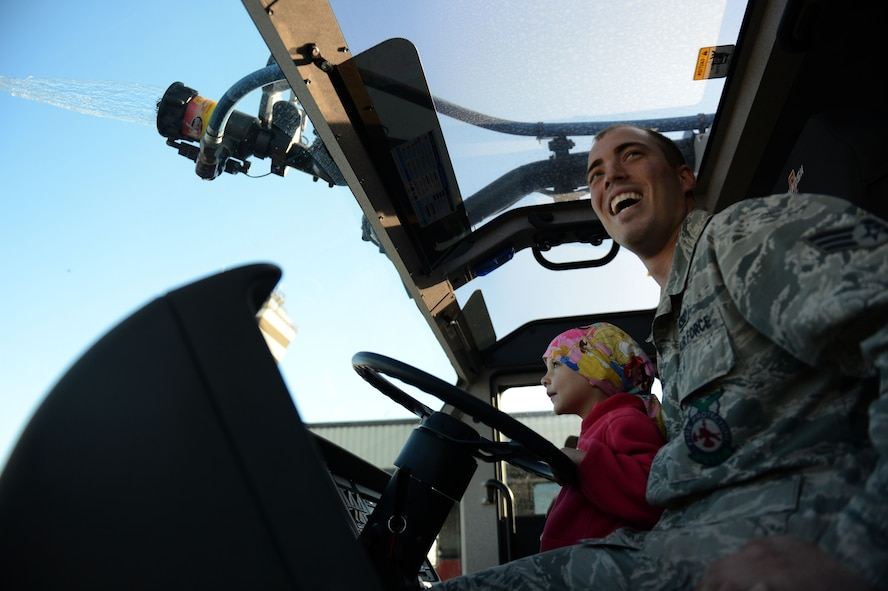 SPANGDAHLEM AIR BASE, Germany – U.S. Air Force Senior Airman Steven Douglass, 52nd Civil Engineer Squadron fire protection technician from Valley City, Ohio, shows Sarah Pittman, 4, how to operate the water cannon aboard a fire truck Aug. 16, 2013. Sarah was diagnosed with leukemia in December 2010. Although she no longer needs IV chemotherapy, she regularly receives checkups and medication at the Mutterhaus der Borrormaerinnen in Trier. (U.S. Air Force photo by Airman 1st Class Gustavo Castillo/Released)