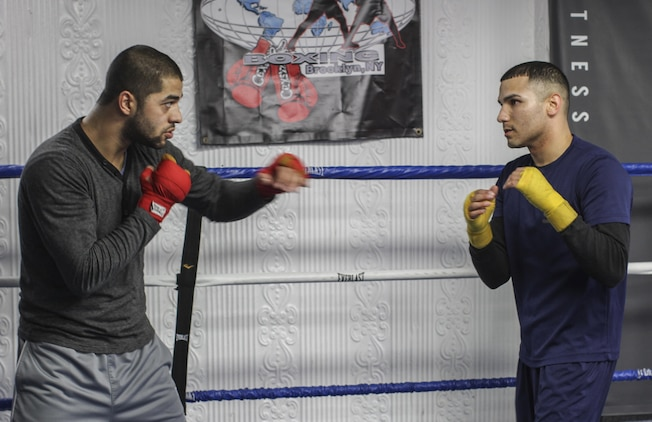 "NEW YORK - Staff Sgt. Todd Dekinderen, a recruiter at Marine Corps Recruiting Substation Brooklyn, Recruiting Station New York, talks about technique with Sadam Ali, an undefeated welterweight pro boxer and member of the 2008 Olympic boxing team, at the Sadam Ali Boxing Center in Brooklyn, Feb. 28.  ""I think he is a really humble, talented man,"" Ali said of Dekinderen.  (U.S. Marine Corps photo by Sgt. Kristin E. Moreno)."