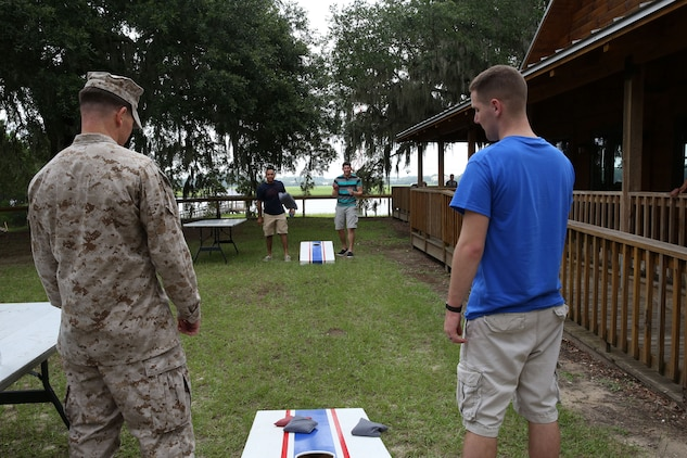 Marines with Marine Aviation Logistics Squadron 31 play cornhole during the squadron's family day held at the Air Station's log cabin, Aug. 16