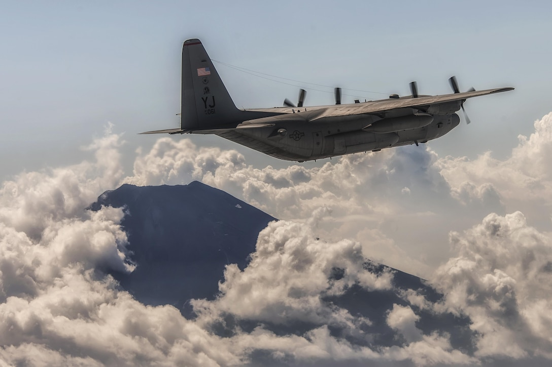 A C-130 Hercules performs a training mission near Mount Fuji, Japan, during a large formation surge flight Aug. 19, 2013. Seven C-130s flew in formation practicing airlift tactics and procedures. (U.S. Air Force photo/Osakabe Yasuo)