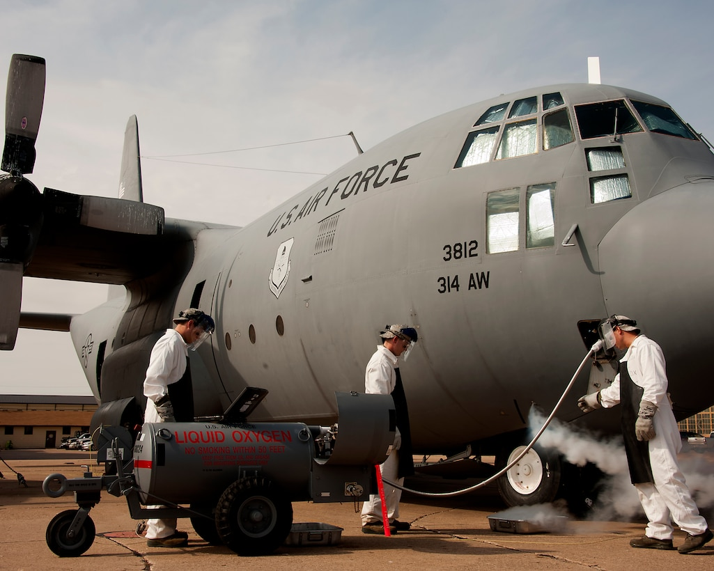 Tech. Sgt. Bryan Lonowski trains Airman Basic Thomas O'Connor and Airman 1st Class Trenton Wyant on how to transfer liquid oxygen to an oxygen reservoir in a C-130 Hercules during the crew chief course, Aug. 14, 2013, at Sheppard Air Force Base, Texas. Students learn the required maintenance requirements step by step in the training manual. Lonowski is assigned to the 362nd Training Squadron. (U.S. Air Force photo/Danny Webb)
