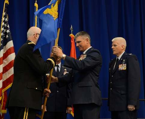 Brig. Gen. Greg Haase , center, hands over his authority as 133rd Airlift Wing Commander to Maj. Gen. Richard Nash, Minnesota Adjutant General in St. Paul, Minn., Aug. 18, 2013. 