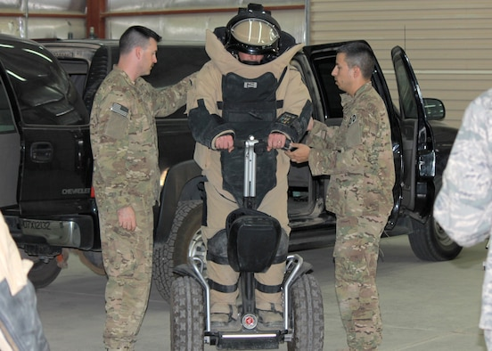 Explosive ordinance disposal Airmen offer assistance as an Airman attempts to operate a Segway while wearing an EOD bomb suit at the 64th Air Expeditionary Group in Southwest Asia, July 26, 2013. The 64th AEG EOD team hosted a two-day open house allowing 64th AEG Airmen an opportunity to learn about their operations and equipment.  (U.S Air Force photo/Staff Sgt. Minerva H. Rosario)