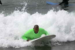 Cpl. Toran Gaal, a dpuble amputee, rides a wave during the Operation Amped surf clinic at San Onofre beach here, Aug. 24. Many veterans use surfing as an escape while others surf as a part of their new lifestyle.